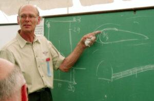 Chris Heintz explaining aerodynamics in front of a chalkboard.