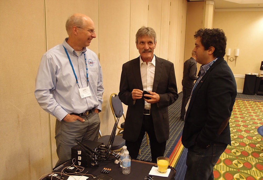 John Palmerless, CAFE board member; Klaus Ohlmann discuss e-Genius with symposium guest.