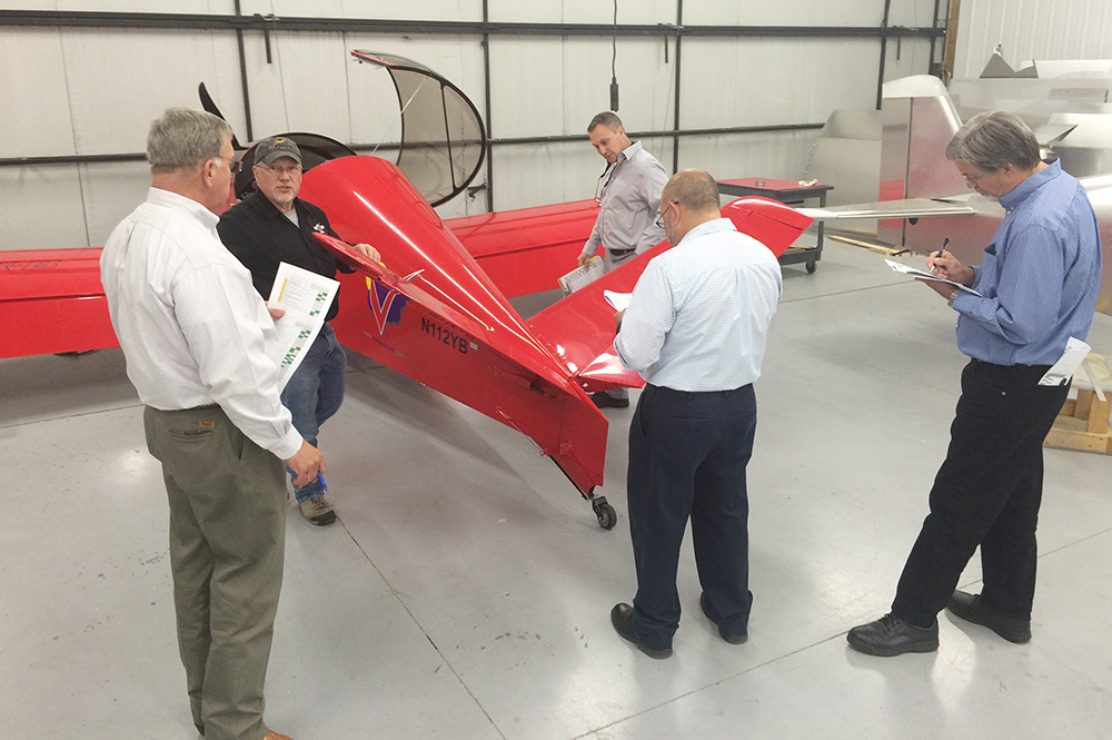 NKET members and trainees examine B-Model empennage and control surfaces, guided by Sonex Aircraft staff.