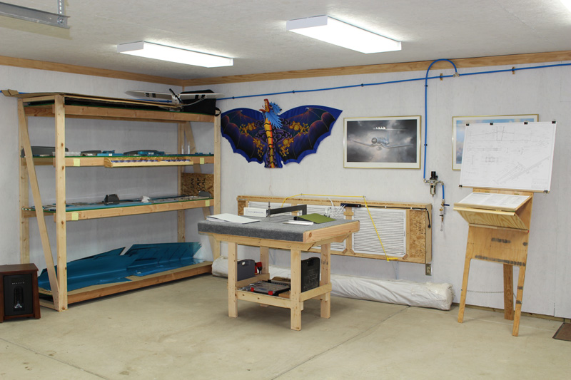One corner of my 25x25 shop, shortly after taking inventory of my RV-8 empennage kit. My custom C-frame/tool table is in the foreground, my plans easel is on the right, and my paint booth fan system is stored against the back wall.