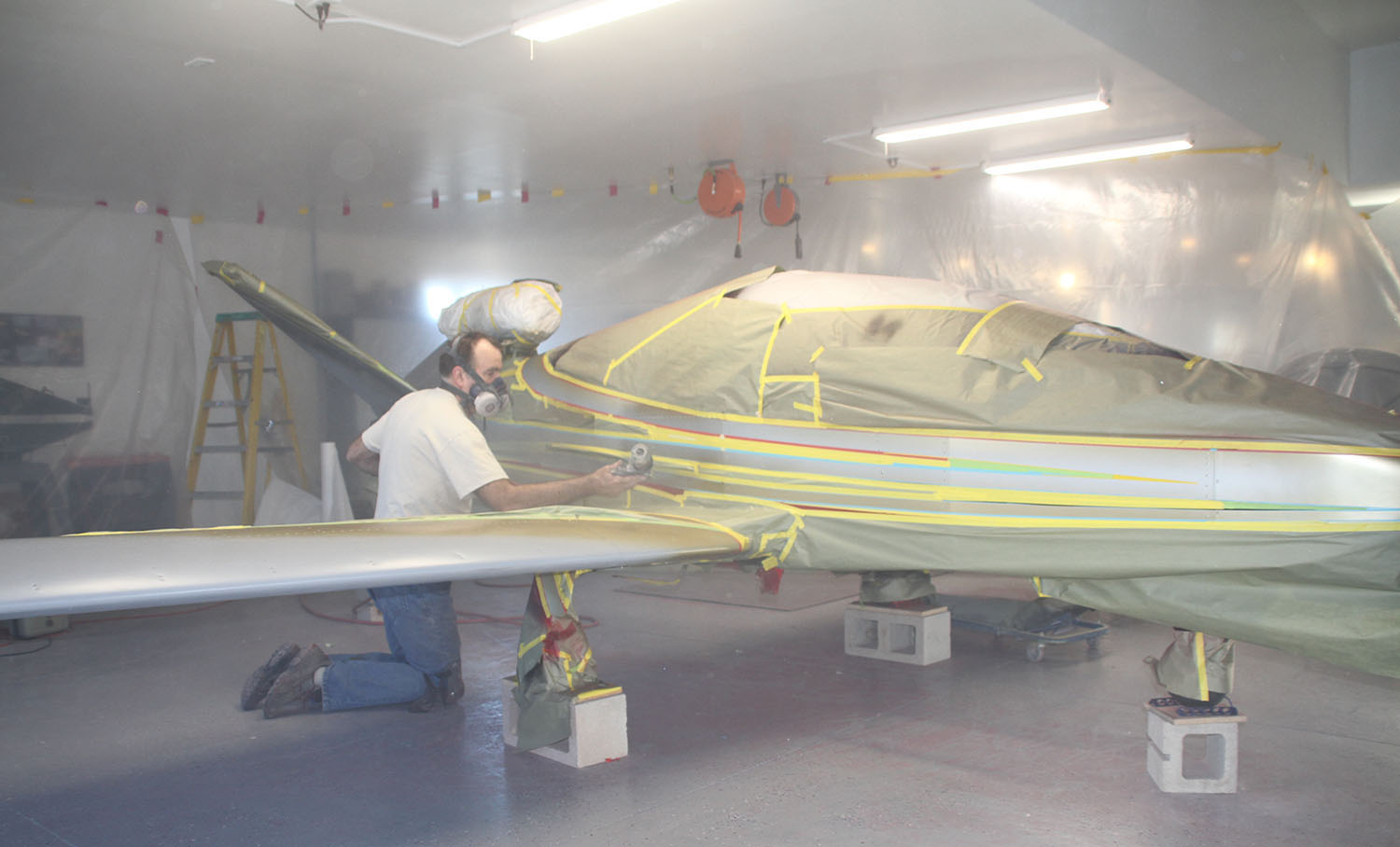 John Stahr sprays white paint as the final area paint on Paul Dye's SubSonex. Most of the jet is masked to protect the earlier laid colors.