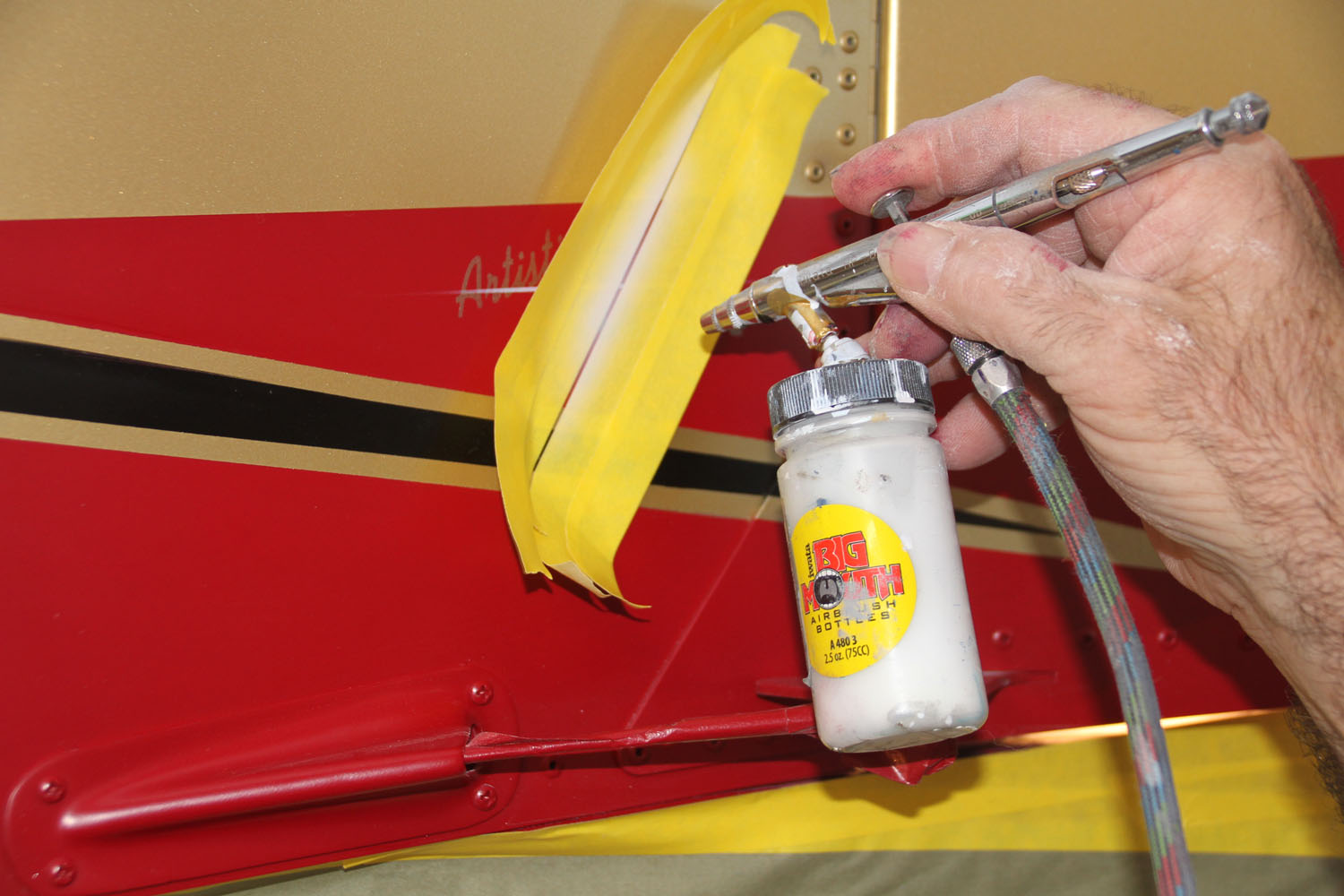 Adding the artist's signature to the back of the fuselage.