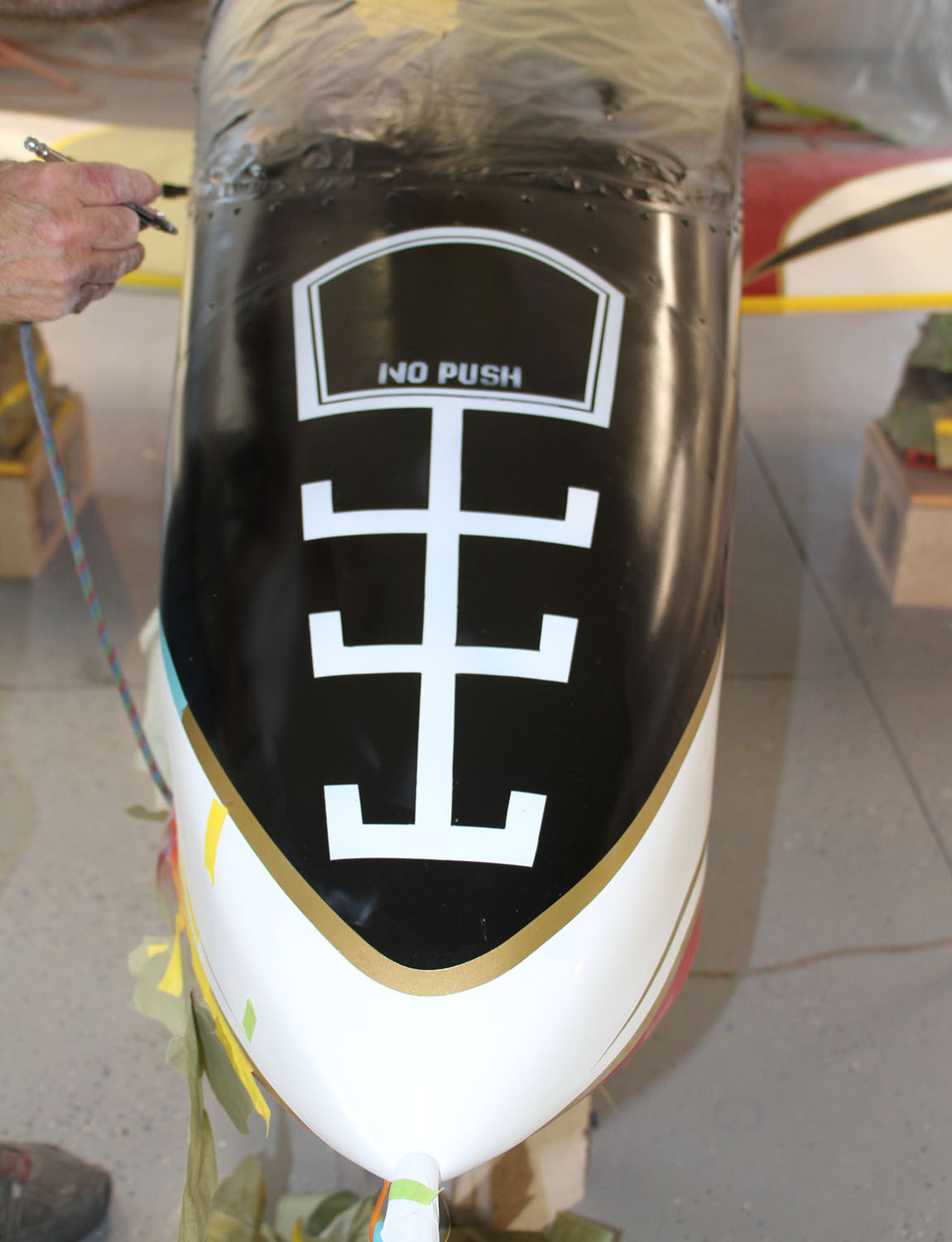 A little nose art with a nod to a re-fueling port. The owner also wants to avoid anyone pushing down on the fiberglass cowl.