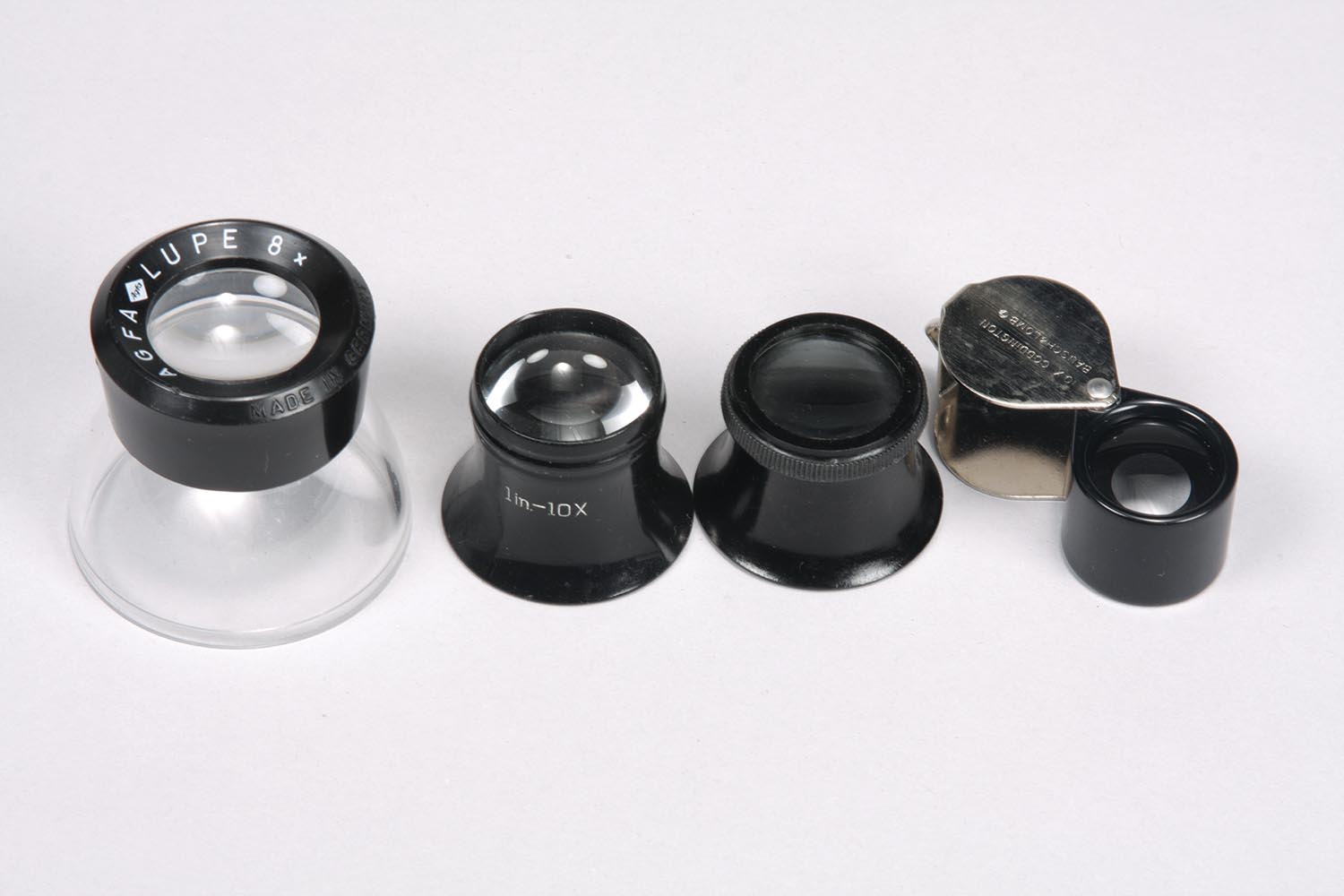 From left to right: A photographer's loupe, two watchmaker's loupes, and a folding pocket loupe.