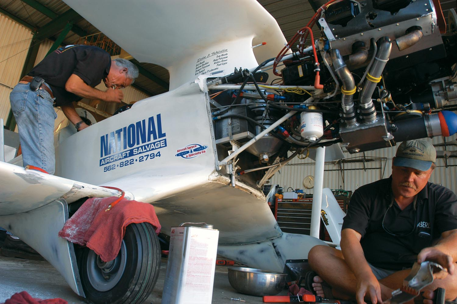Tom Aberle peers into the cockpit while his A&P son Jerry works under the engine. The large canister directly behind the engine is the dry sump system's oil tank. Besides aiding horsepower, the dry sump oiling is one reason Phantom's oil temperature has never been much over 180° F.