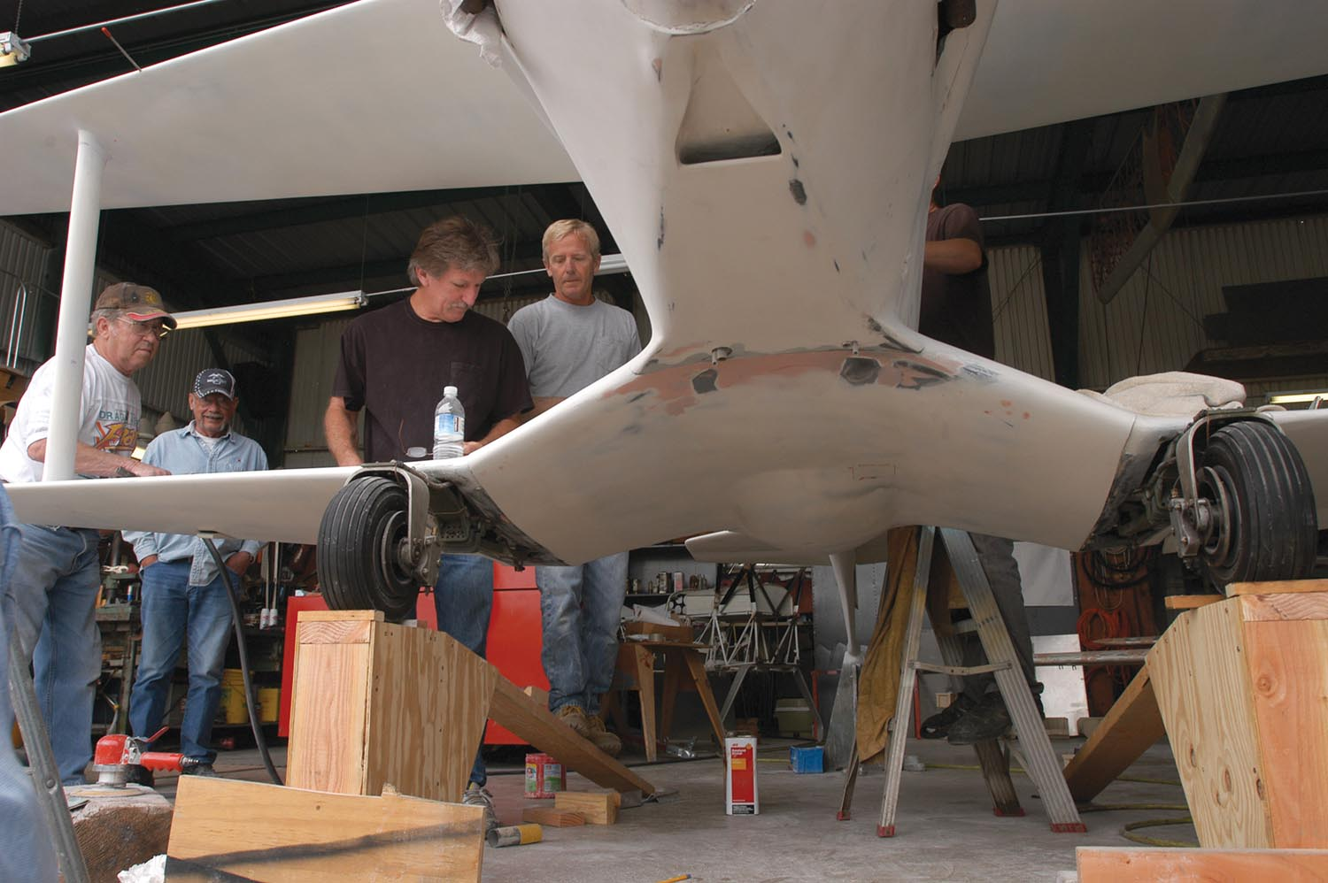 Lee Dorrance, Bob Busch, Andy Paterson, and Steve Wilkenson prep Phantom for its first paint job in 2005. This view shows the oil cooler NACA duct under the cowling and partially shows the cantilever leaf-spring landing gear. A Bob Busch design, the gear was made by cutting up a 4-inch-wide single leaf spring—probably from a pickup truck—and building a multi-bracket, rubber-cushioned attachment that works well. Its drawbacks are the 5.00-5 tires droop more than desirable in flight and it's heavy.