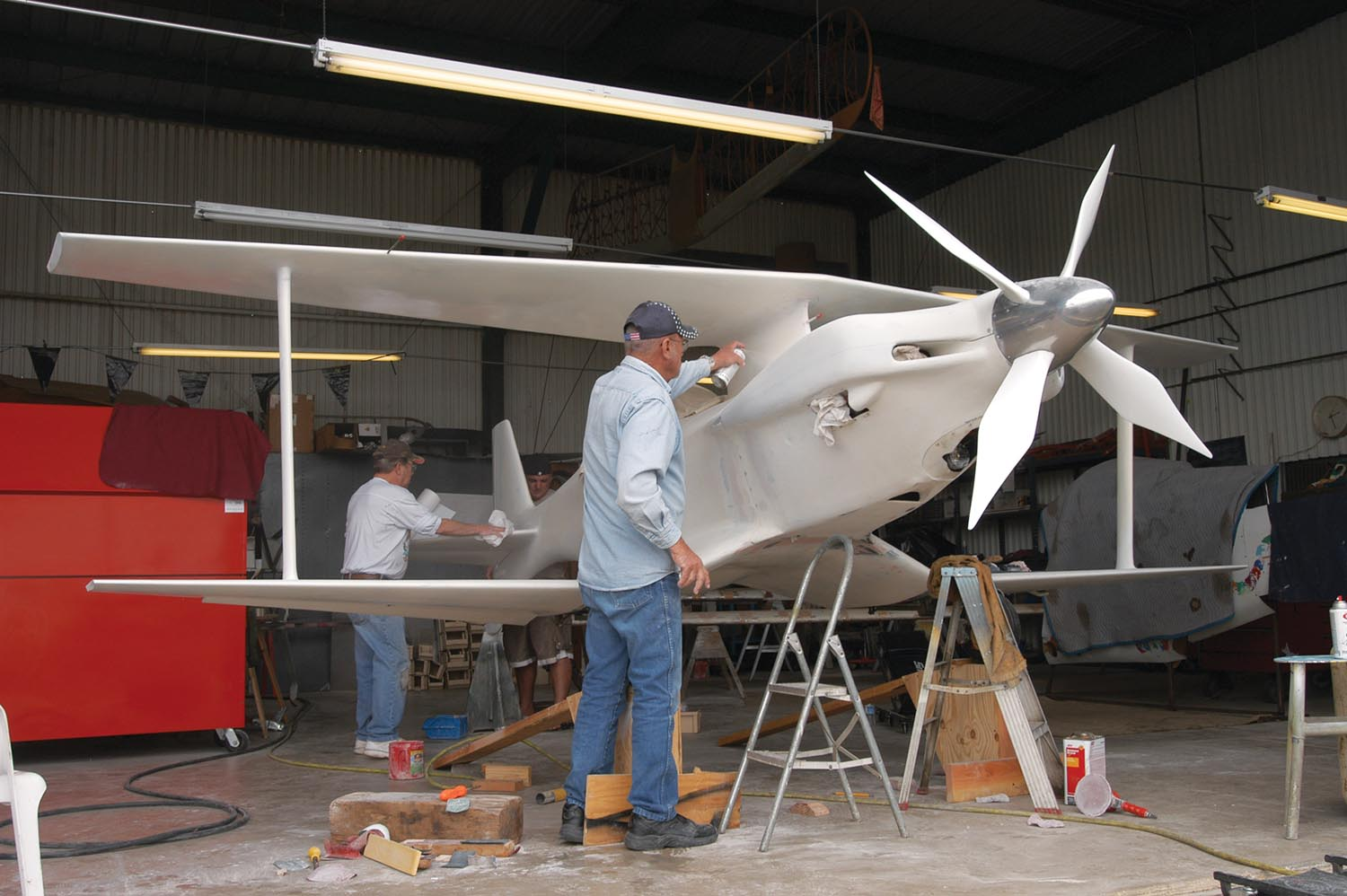 Phantom ran in primer its first two years because there was no time to paint it the first year, and there was still so much other work going on the second year. Here Lee Dorrance preps the tail while Bob Busch works the pylon in preparation for paint in 2005.