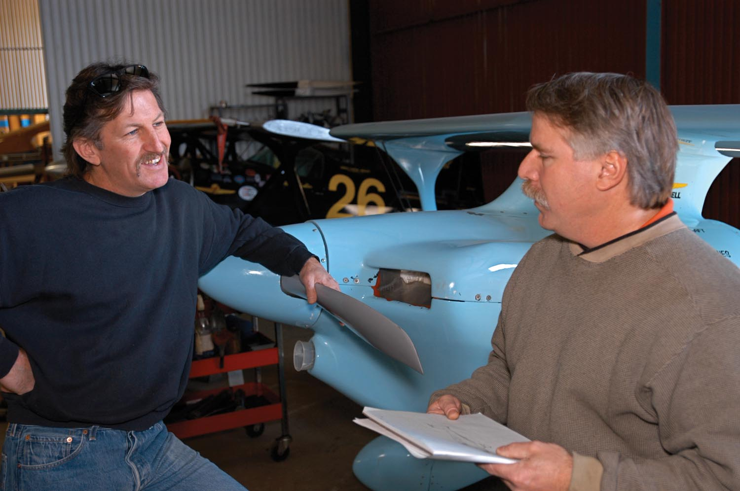 Phantom's futurists, Andy Paterson, left, and Robbie Grove, right, discuss the new air racer during the all-hands meeting in February 2003. Besides composite construction, Andy supplied huge amounts of general labor, and Robbie served as on-call consultant for the trickier engineering bits.