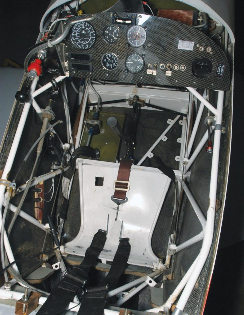 Befitting a dedicated racer, bare essentials mark Phantom's compact cockpit; an EDM 700 engine monitor hiding under the throttle and mixture is the most sophisticated instrument and is used for data logging. Remnants of the Mong white-painted steel-truss fuselage easily stand out against the black carbon fiber skin. As with previous Aberle racers, Phantom uses a one-piece lift-off canopy.