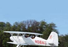 Starduster biplane over grass strip